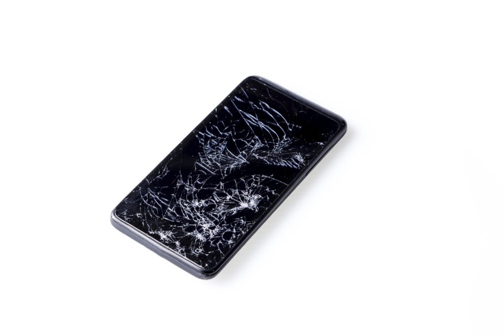 Closeup of mobile smartphone with broken screen isolated on white.